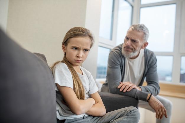 Ophaalproces. grijsharige, bebaarde man praat met zijn dochter en ziet er ontevreden uit