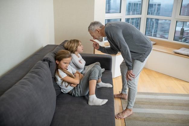 Ophaalproces. grijsharige, bebaarde man praat met zijn kinderen en ziet er ontevreden uit