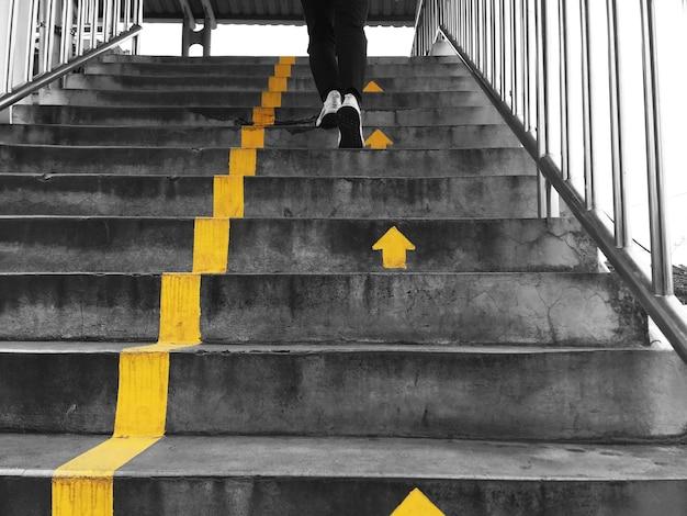 Opkijken naar mensen die op viaduct over de straat lopen en de gele pijlen volgen voor veiligheid en orde.