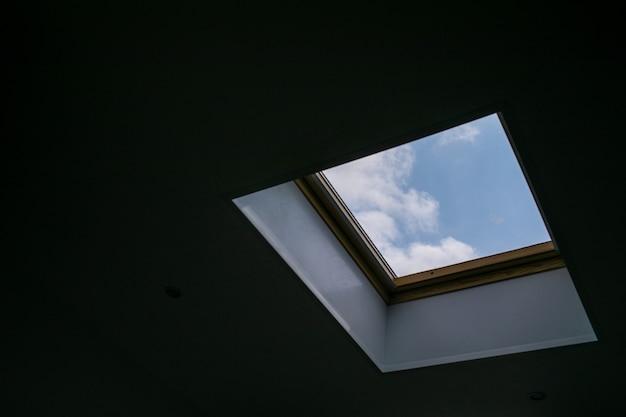 Opkijkend naar de blauwe bewolkte lucht door een modern vierkant plafondraam