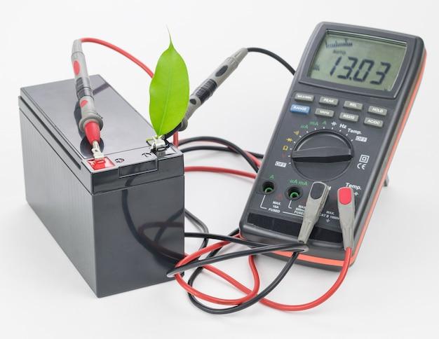 Oplaadbare batterij met aangesloten meetinstrument en groen blad.