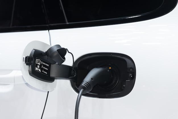 Oplaadpunt elektrische auto. close-up van voeding die in een elektrische auto wordt gestopt.