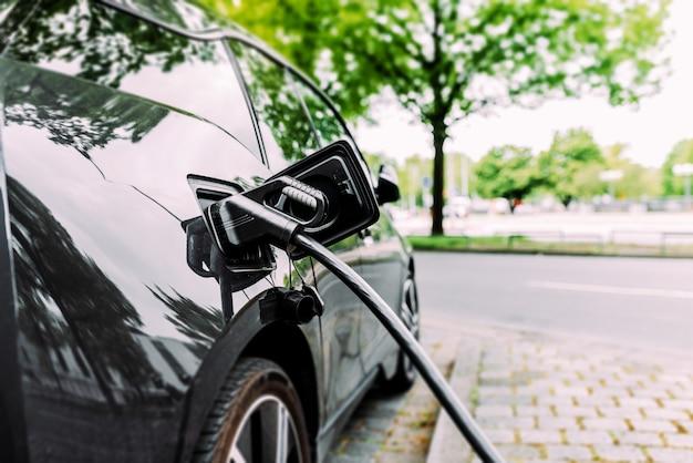 Opladen moderne elektrische auto op straat.