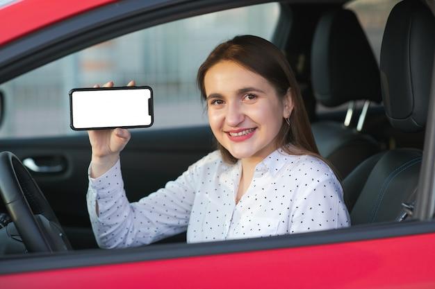 Opladen van elektrische auto en kijken naar app op mobiele telefoon. sluit omhoog van het smartphonescherm. hand die slim apparaat met witte vertoning houdt. mobiele applicatie voor eco-transport