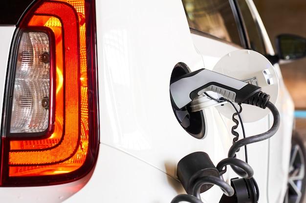 Opladen van elektrische auto of ev op de parkeerplaats of openbare laadpaal. geen uitstoot en milieuvriendelijk voertuig.