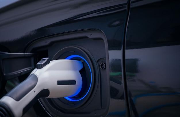 Opladen van moderne elektrische autobatterij op straat die de toekomst van de auto is, close-up van voeding aangesloten op een elektrische auto die wordt opgeladen voor hybride. nieuw tijdperk van voertuigbrandstof.