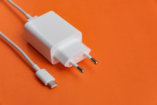 Oplader en usb-kabel type c op oranje achtergrond