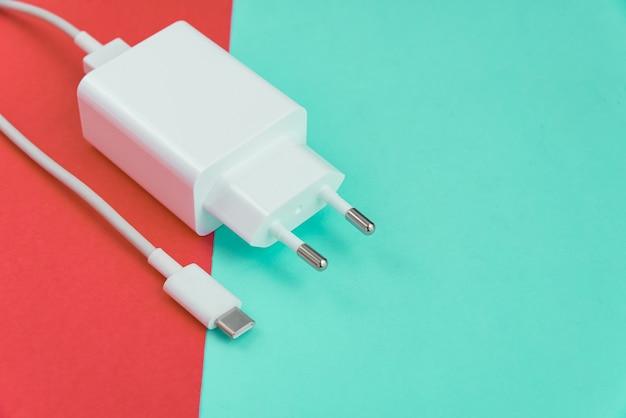 Oplader en usb-kabel type c over roze en blauwe achtergrond