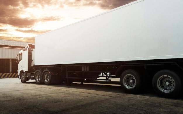 Oplegger vrachtwagens parkeren bij sunset sky road vrachtwagen logistiek en cargo transport concept