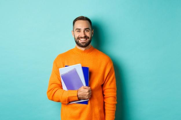 Opleiding. glimlachende bebaarde man met notitieboekjes en lachend, gaande van cursussen, staande over licht turkooizen muur