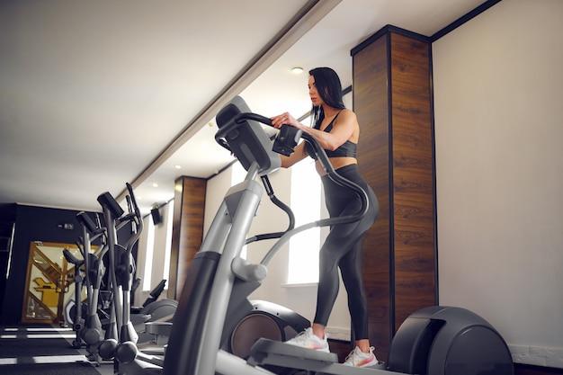Opleiding in de sportschool fitness meisje coach bezig met step machine en toont haar figuur poseren in een sport-pak