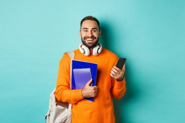 Opleiding. knappe mannelijke student met hoofdtelefoons en rugzak, die smartphone gebruikt
