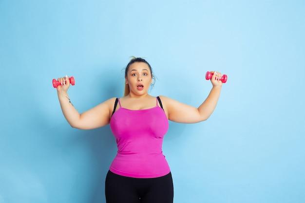 Opleiding van het jonge kaukasische plus grootte vrouwelijke model op blauwe achtergrond. concept van sport, menselijke emoties, expressie, gezonde levensstijl, positief lichaam, gelijkheid. trainen met de gewichten, copyspace.