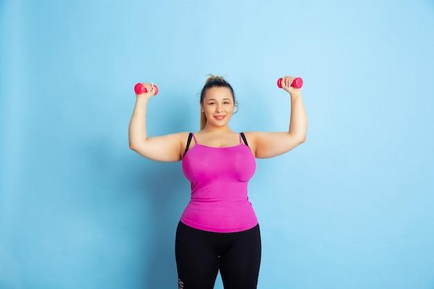 Opleiding van het jonge kaukasische plus grootte vrouwelijke model op blauwe achtergrond