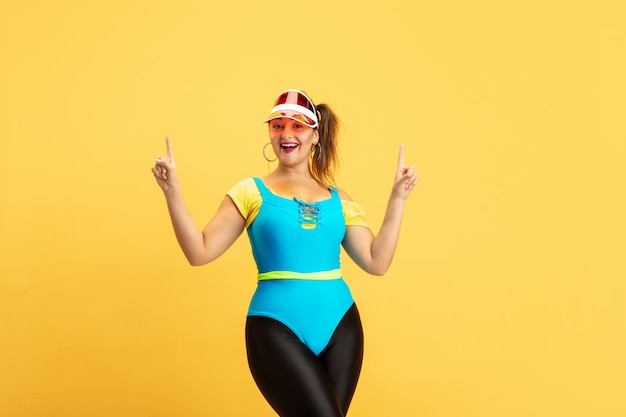 Opleiding van het jonge kaukasische plus grootte vrouwelijke model op geel