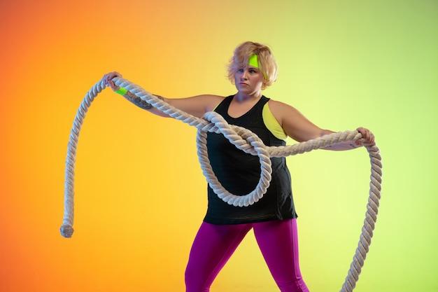 Opleiding van het jonge kaukasische plus grootte vrouwelijke model op oranje achtergrond met kleurovergang in neonlicht. trainingsoefeningen doen met de touwen. concept van sport, gezonde levensstijl, positief lichaam, gelijkheid.