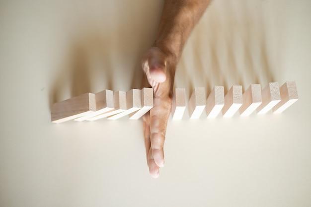 Oplossingsconcept met de hand die voorkomt dat houten blokken in de lijn van domino vallen