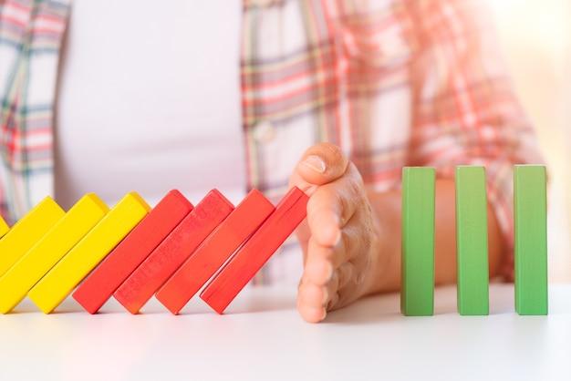 Oplossingsconcept met hand die houten blokken tegenhouden van het vallen in de dominolijn