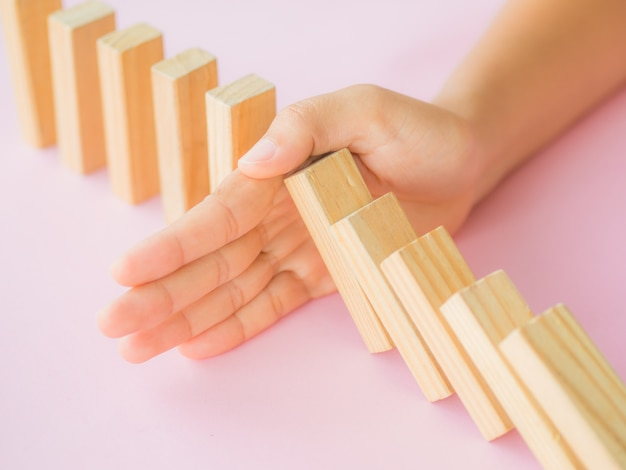 Oplossingsconcept met hand die houten blokken tegenhouden van het vallen in de lijn van domino.