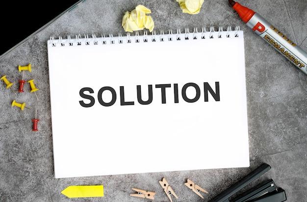 Oplossingstekst op een wit notitieboekje met pinnen, marker en nietmachine op een betonnen tafel.