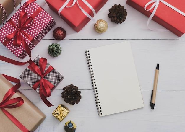 Opmerking boek en pen met kerstmis en nieuwjaar vakantie geschenkdoos met decoratieve versiering op houten tafel