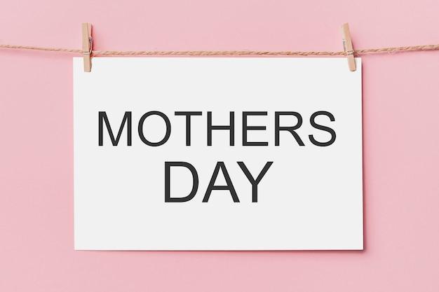 Opmerking brief pin op touw op roze achtergrond, liefde en valentijn concept met tekst moederdag