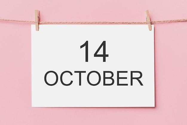 Opmerking brief pin op touw op roze oppervlak, liefde en valentijn concept met tekst 14 oktober 14