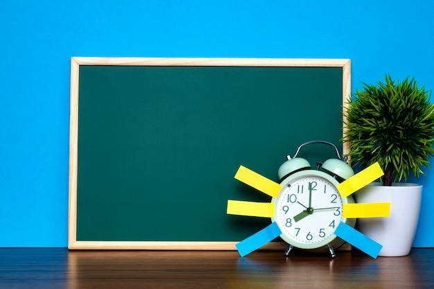 Opmerking papier kleverige en vintage wekker en lege groene schoolbord op tafel