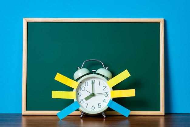 Opmerking papier kleverige en vintage wekker en lege groene schoolbord