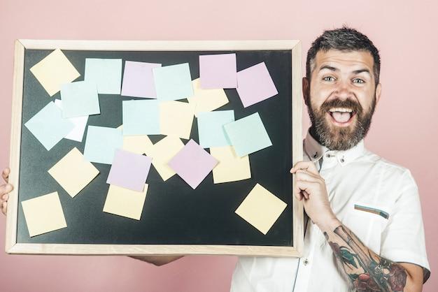 Opmerkingen. business, planning, management, herinnering en mensen concept. gelukkig bebaarde man houdt bord met plaknotities. bedrijfsconcept. bankconcept. geld besparen concept. financiën.