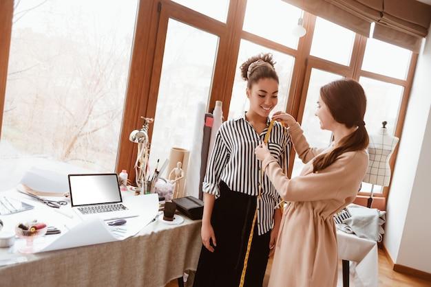 Opmeten voor nieuwe jurk. jonge modeontwerper die metingen doet voor een afrikaans model