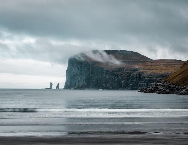Opname van de prachtige natuur zoals de kliffen, zee, bergen van de faeröer