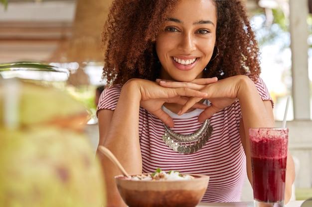 Opname van een aangenaam uitziende tiener heeft knapperig haar, lacht breed, toont witte perfecte tanden, houdt beide handen onder de kin, brengt vrije tijd door in café met terras, eet een exotisch gerecht en drinkt een cocktail