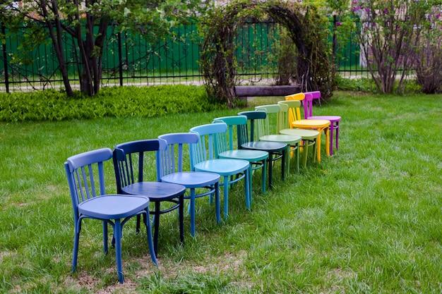 Opnieuw geverfde gerenoveerde houten weense stoelen kleurrijke stoelen staan op het grasveld als symbool van geweten...