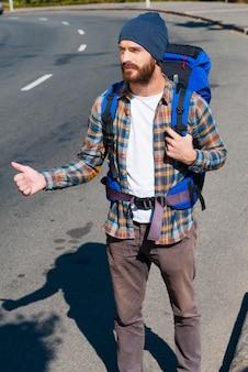 Oppakken. knappe jongeman met rugzak die zijn hand uitstrekt met duim omhoog terwijl hij op de weg staat