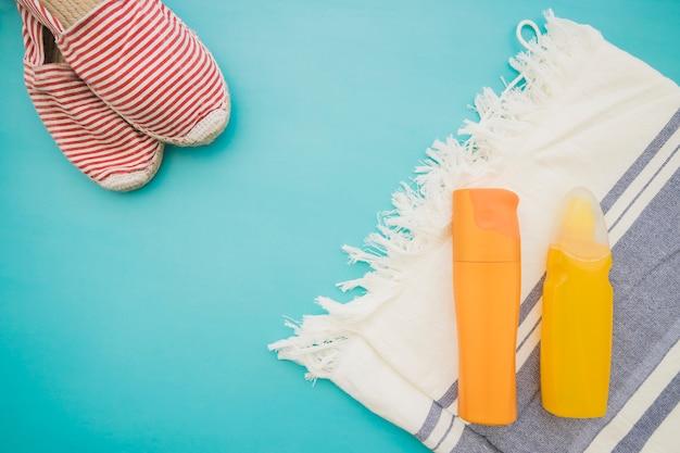 Oppervlak met handdoek, lotions en zomer schoenen