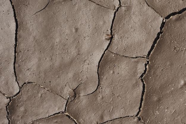 Oppervlak of textuur van nat grijs gebarsten vuil of grond