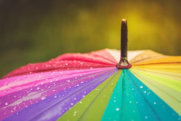 Oppervlak van regenboog paraplu met regendruppels erop.