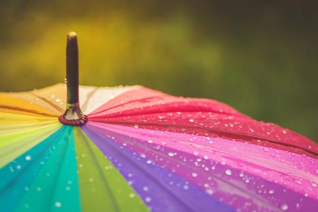 Oppervlak van regenboog paraplu met regendruppels erop