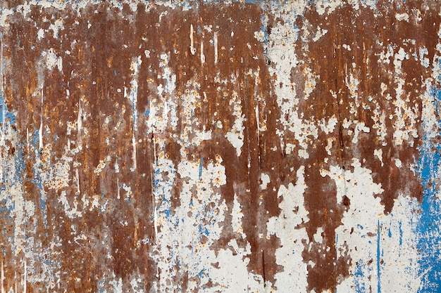 Oppervlak van stalen wand met afbladderende verf en corrosie.