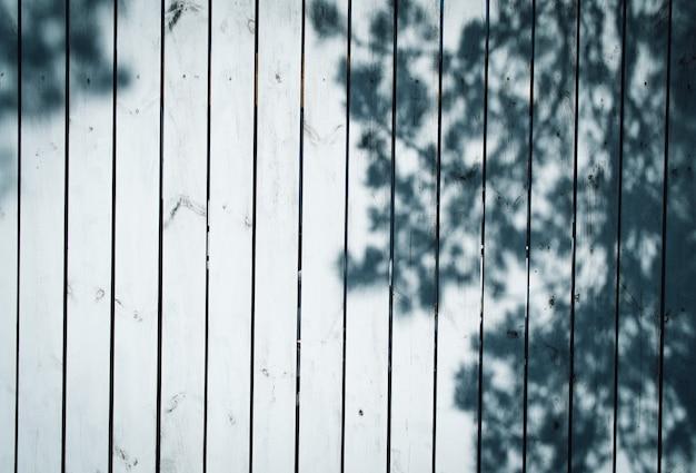 Oppervlak van witte houten planken met de schaduw van een boom.
