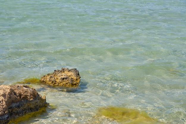 Oppervlakte van helder water op tropisch zandstrand met stenen in kreta griekenland.