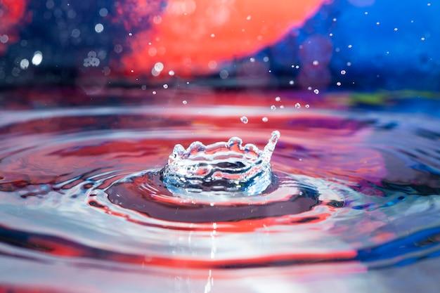 Oppervlakte water met spatten en kleurrijke achtergrond