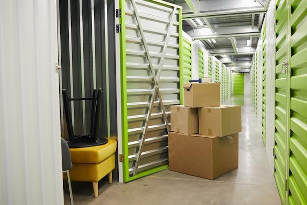 Oppervlaktebeeld van kartonnen dozen gestapeld door open deur van self storage unit, kopieer ruimte