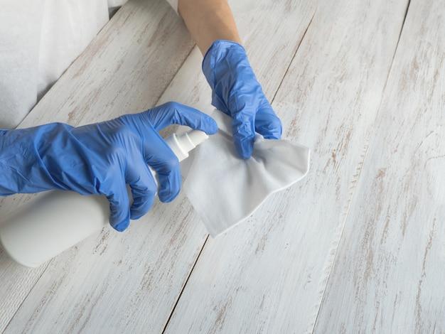 Oppervlaktereiniging spuiten antibacterieel ontsmettende spuitfles desinfecterend tegen covid-19 verspreiding met medische blauwe handschoenen