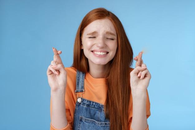 Oprecht hoopvol schattig roodharige meisje geloof wonder ogen sluiten trouw bidden kruis vingers geluk hoop droom uitkomen maak wens gretig horen positieve resultaten anticiperen blauwe achtergrond