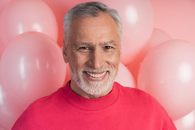 Oprechte, aantrekkelijke man die lacht op een muur van roze ballonnen