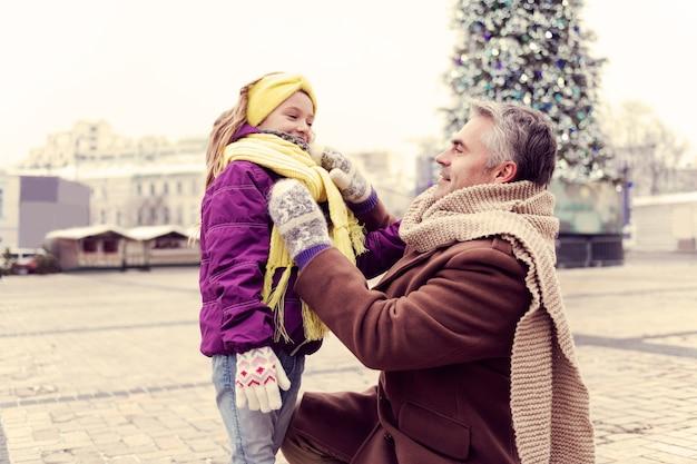 Oprechte communicatie. geweldig blond meisje permanent in halve positie en luistert naar haar vader