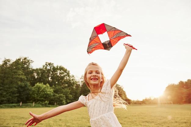 Oprechte glimlach. gelukkig meisje in witte kleren veel plezier met vlieger in het veld. prachtige natuur.
