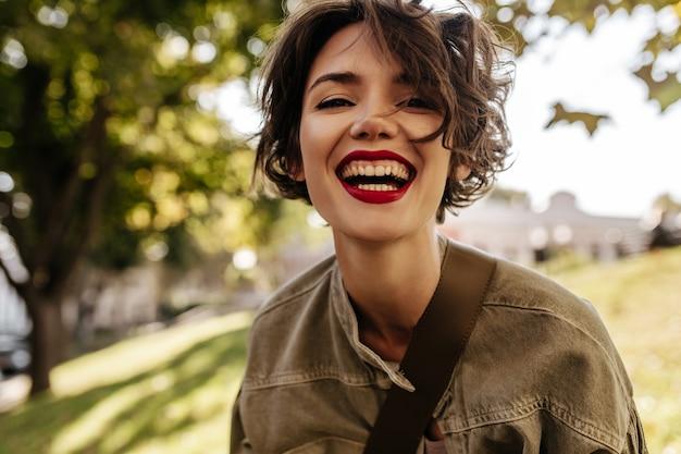 Oprechte vrouw met kort krullend kapsel en rode lippenstift die buitenshuis lacht. blije vrouw in olijfkleren buiten.